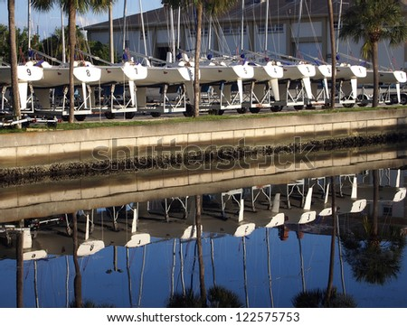 Ten sailboats on trailers reflected in a quiet channel.