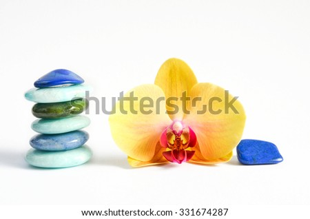 Tender yellow blossom of orchid with healing power gemstones/Yellow and blue decoration/Health and wellness gemstones