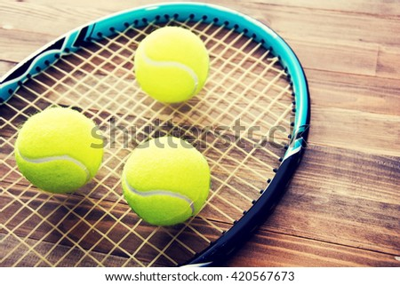 Tennis game. Tennis balls and racket on wooden background. Vintage retro picture.