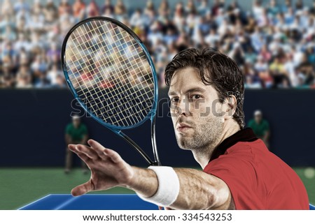 Tennis player with a red shirt, playing on a fast tennis court.