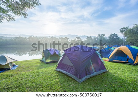 Tents in forest. around the edge of the reservoir and the timber in bright morning.