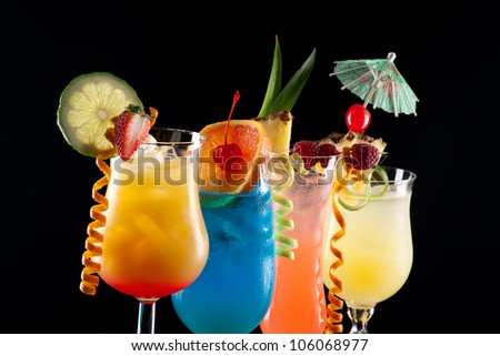 Tequila Sunrise, Blue Lagoon, Rum Runner, and Bahama Mama cocktails over black background on reflection surface