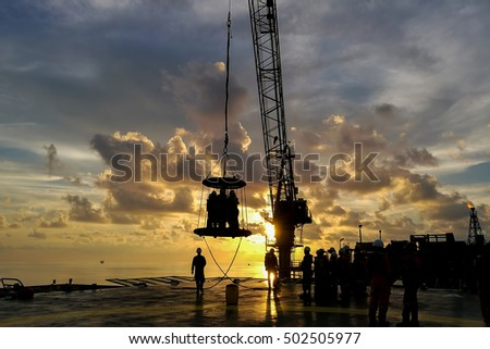TERENGGANU, MALAYSIA - July 18, 2016 - Silhouette of basket transfer activities on a day to day movement of workers from accommodation vessel or boat to oil and gas platforms or rigs at offshore.