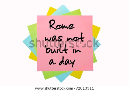 "text "" Rome was not built in a day "" written by hand font on bunch of colored sticky notes"