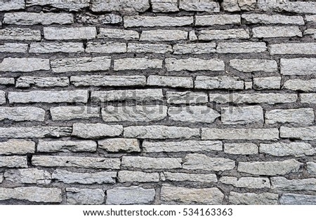 Texture of gray ancient city wall in Pskov