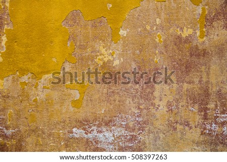 texture of the old brown and yellow paint on a concrete wall with irregularities