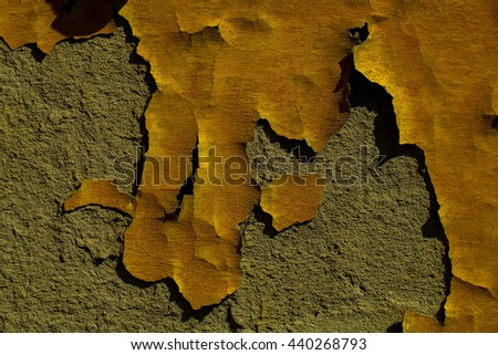 Textured background of old painted stucco wall with yellow weathered aged paint