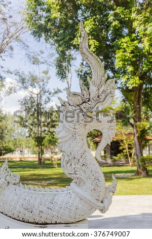 Thai Art, Single white Naka (giant snake) head statue at Thai Buddhist church with shallow depth of field, Tha Sak temple, Phuket province, South of Thailand