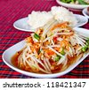 Thai famous food, spicy papaya salad or Somtam with sticky rice - stock photo