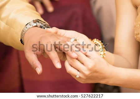 Thai groom wearing wedding ring for his bride hand