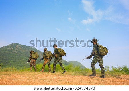 Thai soldier holding gun and carry bag in full army uniform in training with field background
