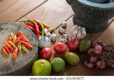 Thailand Food Ingredients: Tomatoes, peppers, garlic, shallots, lemon, olive with a mortar on a wooden floor.