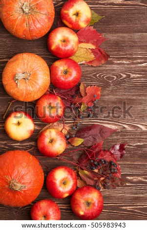 Thanksgiving background with apples, pumpkins and fallen leaves on wooden background. Autumn background