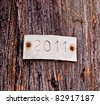The Aluminum plate of 2011 on old wood background - stock photo