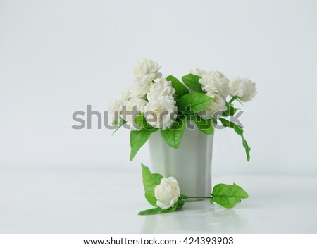 the artificial jasmine flower in the pot at the white table with the white wall background.