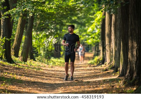 The athletic man run on the beautiful park alley