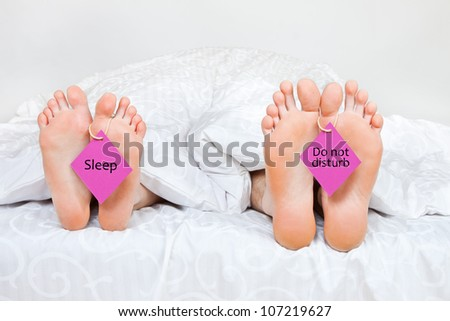 The bared heels of pair in stick out from under bed-sheets