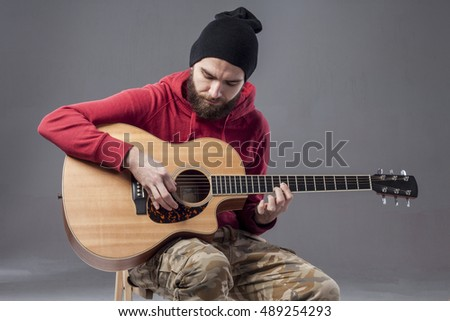 The Bearded Guy With A GuitarThe Guitarist In Hat On BackgroundHandsome
