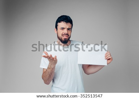The bearded student in a white T-shirt holding a blank sheet of paper.  isolated on a light background  .