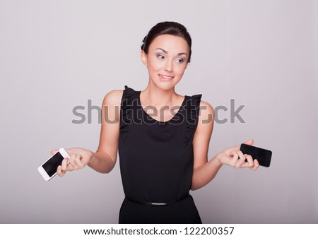 the beautiful girl holds two phones