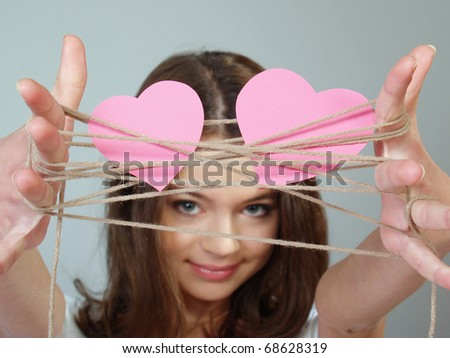 The beautiful girl holds two pink hearts weaved by threads in her hands