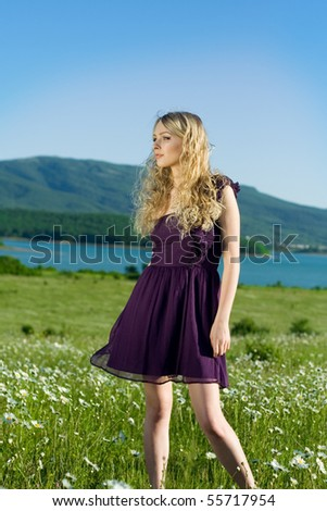 The beautiful girl in the field with camomiles against mountains and lake