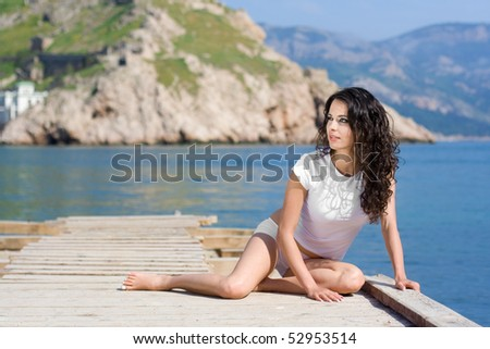 The beautiful girl sits on a pier near the sea