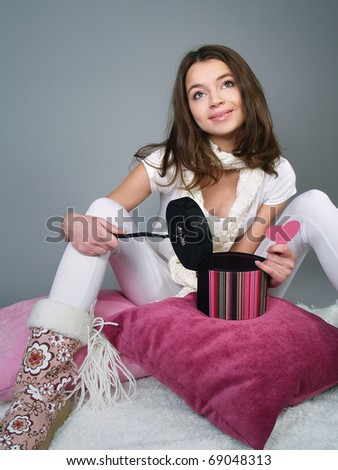 The beautiful girl sits on pillows with an open box and a heart in her hands