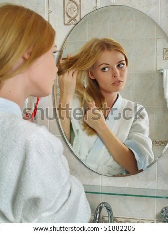 The beautiful girl with blond hair looks in a mirror in a bathroom
