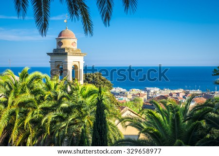 the belfry and church's roof is hiding behind the palms, sanremo, italy
