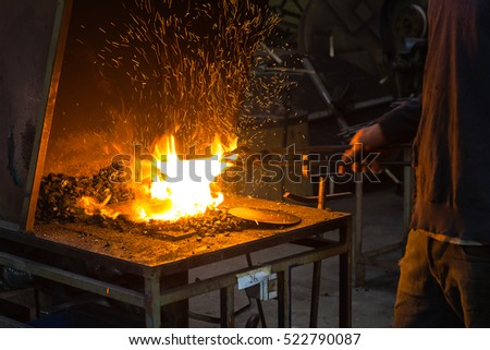 The blacksmith making flames in smithy with spark fireworks
