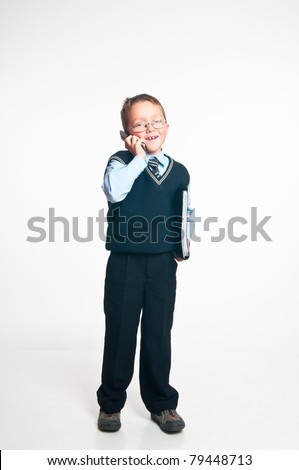 The boy speaks on the phone and has control over a folder for papers in hands on a white background