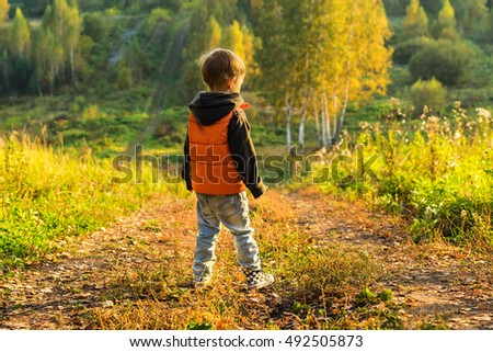 The boy standing on the road at the edge of the forest, sunny autumn day Yellow leaves underfoot.
