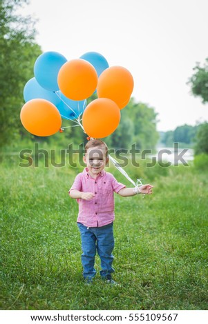The boy with balloons in nature. The little boy smiling in the forest.  The boy on the bank of the river.