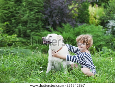 The boy with blond curly hair in a striped vest with a white dog in the garden in summer, child and his pet friend in the park