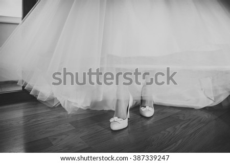 The bride getting her wedding shoes on. The bride is putting on her shoes for the wedding day. Black and white vintage photography