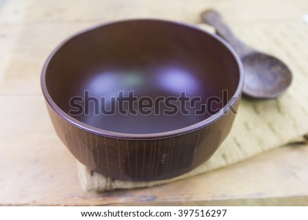 The brown wooden bowl and spoon on a rustic table closeup