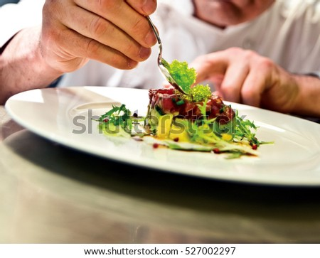 The chef prepares a meal. Slim subtle touches for a special presentation.