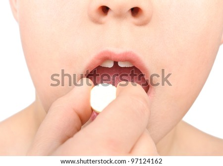 The child puts the pill into his mouth. Close-up Photos