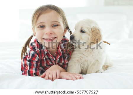 The child with the dog lying  at home