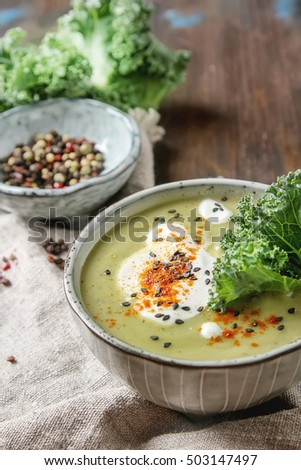 The classic pea puree soup in the gray plate with a dollop of sour cream, spices, cabbage Kale. Dark wood background