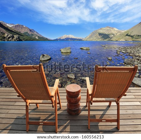 The comfortable place to enjoy the beauty of the lake and clouds in Patagonia. Two folding wooden chairs and a small bedside table on the boardwalk
