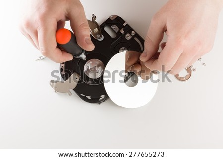 the computer hard drive in the course of dismantling on a white background
