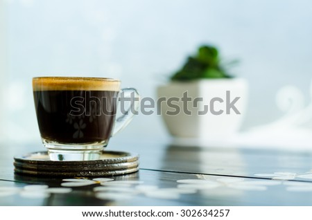 The cup of coffee (espresso) on wooden table in the coffee shop
