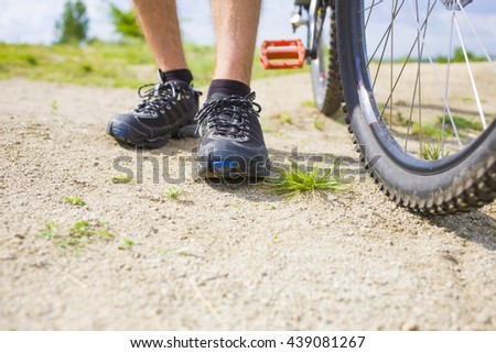 The cyclist is standing near his bike before a trip to the mountains.