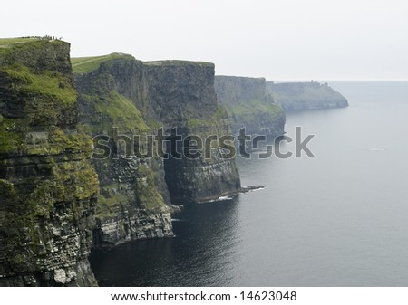 The dark, ominous Cliffs of Moher are a landmark in Western Ireland with sheer rock walls that rise 600 feet from the ocean. A group of people in the field at the upper left provide a sense of scale.