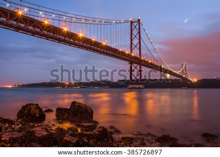 The 25 de Abril bridge over Tagus river and big Christ monument in Lisbon at sunset, Portugal