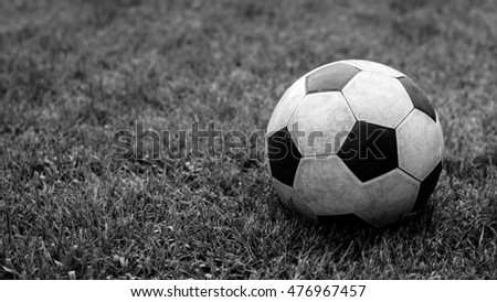 The dirty soccer ball on the grass; Black and white tone