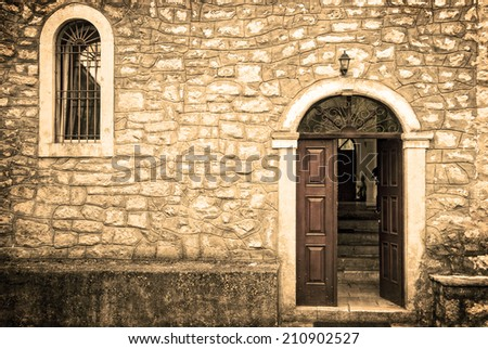 The door and window of an antique stone church on a grungy background