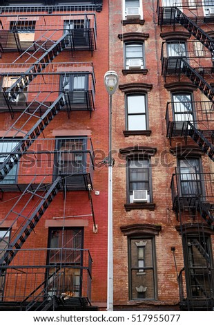 The facades of two highrise apartment buildings in New York City, with outside fire escapes made of steel